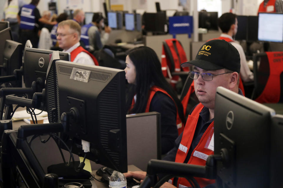 FILE - In this Oct. 10, 2019, file photo, Pacific Gas & Electric employees work in the PG&E Emergency Operations Center in San Francisco. When Pacific Gas & Electric set up emergency operations centers to coordinate intentional blackouts intended to prevent wildfires in Northern California, the nation's largest utility forgot one thing, emergency managers who knew the fundamentals of emergency management in California. (AP Photo/Jeff Chiu, File)