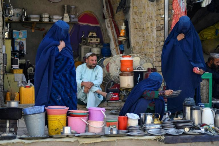 Burqa-clad women look at secondhand household items at a stall in a market in Kandahar (AFP/JAVED TANVEER)