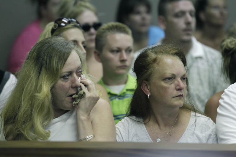 "Laura Robichaud, left, sister of Chris Hall, wipes her face as Roger Bowling is arraigned in 24th District Court in Allen Park, Mich., Monday, July 23, 2012 for the deaths of Hall and Danielle Greenway who were found last week in the Detroit River. Police say they found ""copious amounts"" of blood in a Detroit-area home where Bowling is charged with fatally shooting the couple and dismembering the bodies. (AP Photo/Carlos Osorio)"
