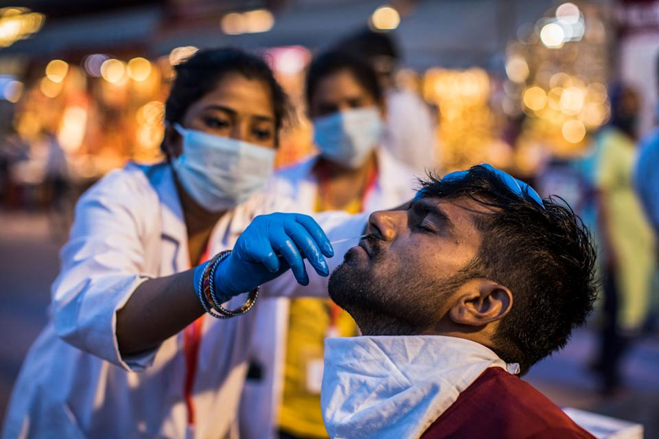 A health worker collects a nasal swab sample from a Hindu devotee to test for the Covid-19 coronavirus during the ongoing religious Kumbh Mela festival in Haridwar on April 12, 2021. (Photo by Xavier GALIANA / AFP) (Photo by XAVIER GALIANA/AFP via Getty Images)