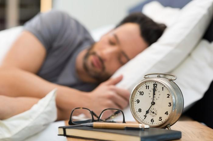 A man sleeping with an alarm clock and glasses in the foreground.