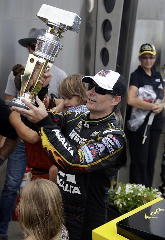 Jeff Gordon holds up the trophy after winning the NASCAR Brickyard 400 auto race at Indianapolis Motor Speedway in Indianapolis, Sunday, July 27, 2014. (AP Photo/Darron Cummings)