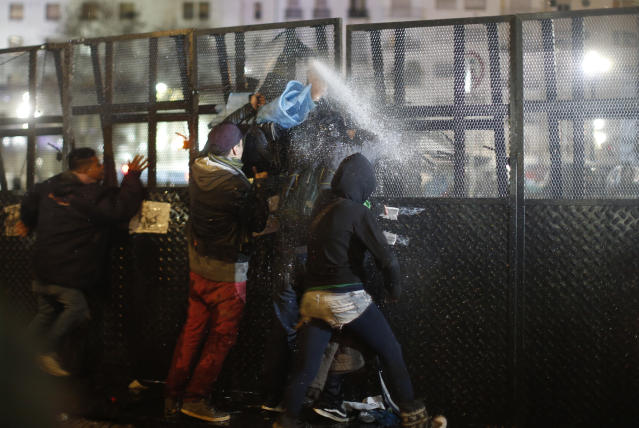 <p>Pro-choice activists confront security forces spraying water from the other side of a mobile barrier wall set up outside Congress, after lawmakers voted against a bill that would have legalized elective abortion in the first 14 weeks of pregnancy, in Buenos Aires, Argentina, early Thursday, Aug. 9, 2018. (Photo: Natacha Pisarenko/AP) </p>