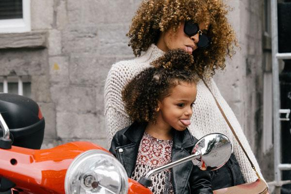Mothering Daughters Is Much More Complex Than Sparkles, Shopping Sprees, And Princesses: Two women, and mother and daughter looking into mirror and making faces