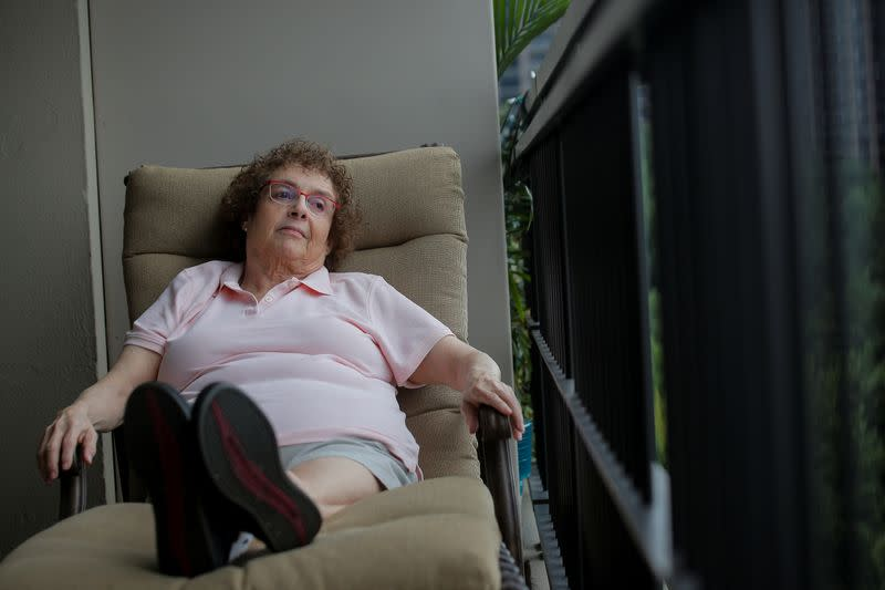 Laura Gross sits down after feeling weak while posing on her balcony in Fort Lee, New Jersey