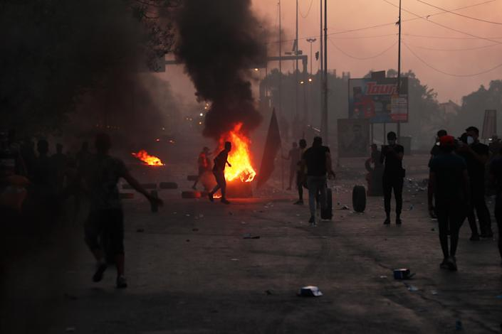 Anti-government protesters set fires and close a street during a demonstration in Baghdad, Iraq, Saturday, Oct. 5, 2019. The spontaneous protests which started Tuesday in Baghdad and southern cities were sparked by endemic corruption and lack of jobs. Security forces responded with a harsh crackdown, with dozens killed. (AP Photo/Hadi Mizban)