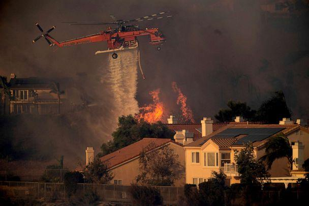 PHOTO: A helicopter drops water while battling a wildfire called the Saddle Ridge Fire in Porter Ranch, Calif. on Oct. 11, 2019. (Noah Berger/AP, FILE)