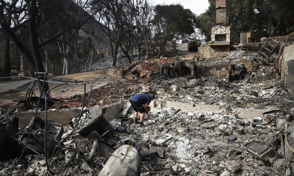 "<span class=""element-image__caption"">Roger Kelton searches through the remains of his mother-in-law's home leveled by the Woolsey Fire, in Agoura Hills, near Cornell, California.</span> <span class=""element-image__credit"">Photograph: Jae C Hong/AP</span>"