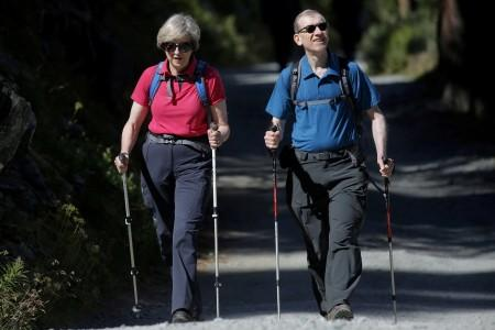 FILE PHOTO: Britain's Prime Minister Theresa May walks in a forest with her husband Philip at the start of a summer holiday in the Alps, in Switzerland