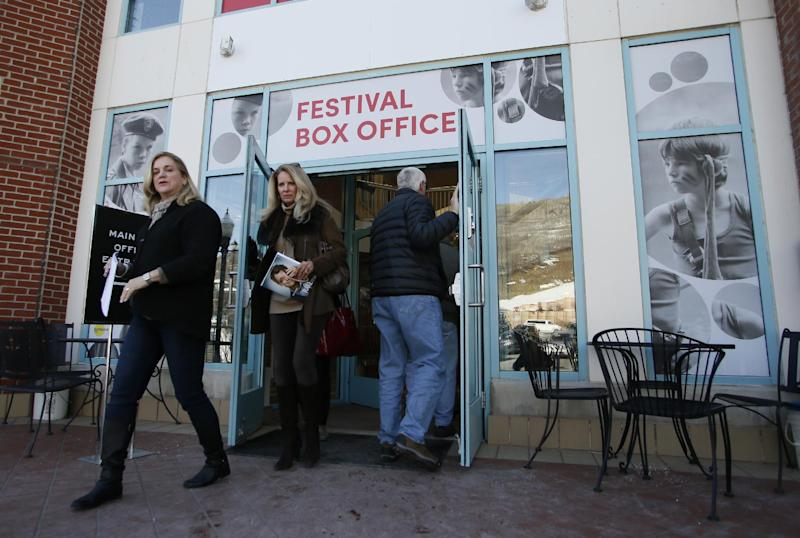 Visitors walk out of an entrance to the 2014 Sundance Film Festival box office on Thursday, Jan. 16, 2014, in Park City, Utah. The independent film festival runs Jan. 16-26, 2014. (Photo by Danny Moloshok/Invision/AP)