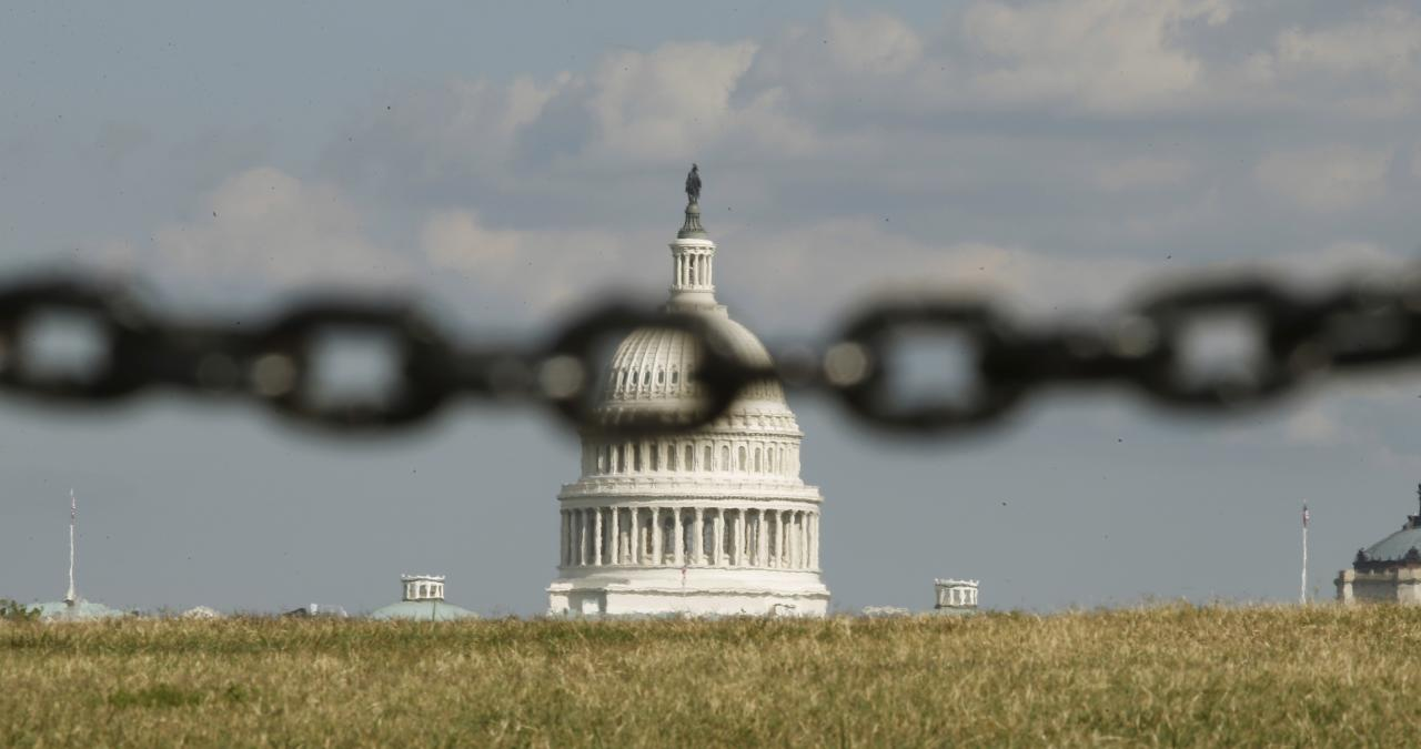 The U.S. Capitol is photographed through a chain fence in Washington September 30, 2013. As many as a million government employees were making urgent plans on Monday for a possible midnight shutdown, with their unions urging Congress to strike a last-minute deal. REUTERS/Kevin Lamarque (UNITED STATES - Tags: POLITICS BUSINESS TPX IMAGES OF THE DAY)