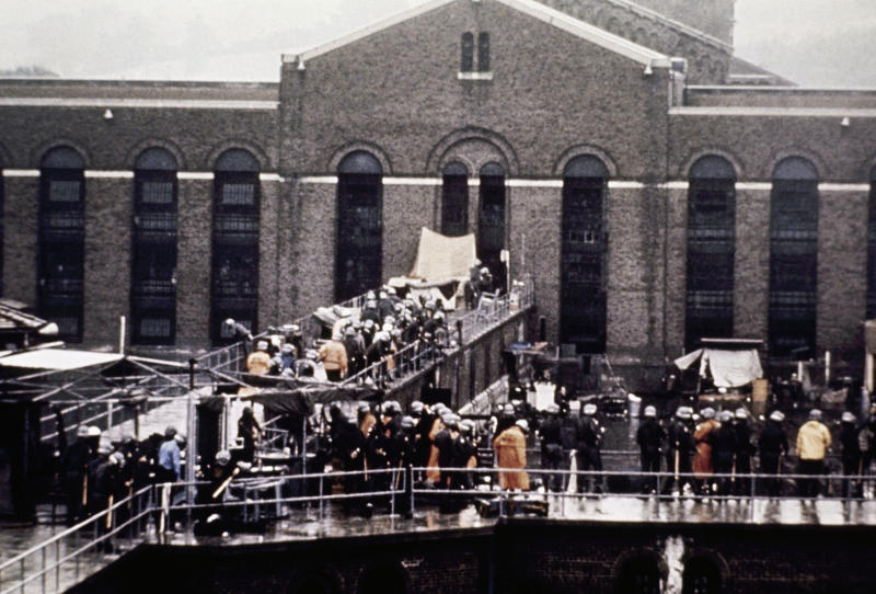 FILE - In this Sept. 13, 1971 file photo, prison guards and New York State troopers gather outside Attica State Prison after retaking it from inmates who rioted and held the prison for five days, in Attica, N.Y. New York's Attorney General Eric Schneiderman has asked a state judge to unseal documents about the 1971 riot and retaking of Attica state prison in the nation's bloodiest prison rebellion. (AP Photo, File)