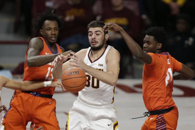 Minnesota forward Alihan Demir (30) rebounds against Clemson forwards Tevin Mack (13) and Khavon Moore (21) in the first half during an NCAA basketball game Monday, Dec. 2, 2019, in Minneapolis. (AP Photo/Andy Clayton-King)