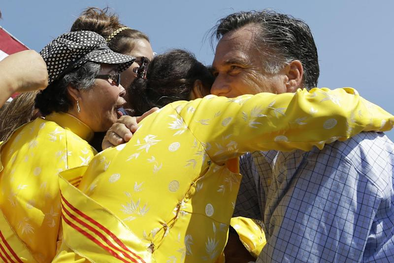 "Republican presidential candidate, former Massachusetts Gov. Mitt Romney embraces women wearing traditional Vietnamese ""ao dai"" dresses as he campaigns at Van Dyck Park in Fairfax, Va., Thursday, Sept. 13, 2012. (AP Photo/Charles Dharapak)"
