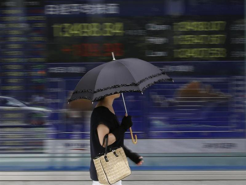 A woman walks past a stock quotation board outside a brokerage in Tokyo