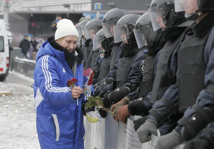 A pro-European Union activist gives flowers to riot police which block a main street in central Kiev, Ukraine, Tuesday Dec. 10, 2013. Top Western diplomats headed to Kiev Tuesday to try to defuse a standoff between President Viktor Yanukovych's government and thousands of demonstrators, following a night in which police in riot gear dismantled protesters' encampments outside government buildings. (AP Photo/Efrem Lukatsky)