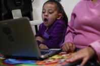 Liz, 5, yawns as she follows along with an online pre-kindergarten class, as students return to classes but not schools in Mexico City, Monday, Aug. 24, 2020. A system cobbling together online classes, instruction broadcast on cable television channels and radio programming in indigenous languages for the most remote, will attempt to keep students from missing out. (AP Photo/Rebecca Blackwell)