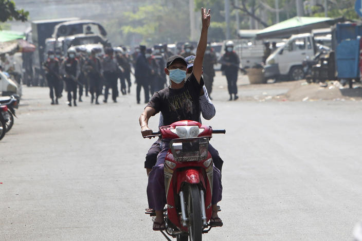 A protester on a motorbike flashes the three-fingered salute while soldiers and police take position to disperse protesters on one of the main roads in Mandalay, Myanmar, Friday, Feb. 26, 2021. Security forces in Myanmar's largest city Yangon on Friday fired warning shots and beat truncheons against their shields while moving to disperse more than 1,000 anti-coup protesters. (AP Photo)