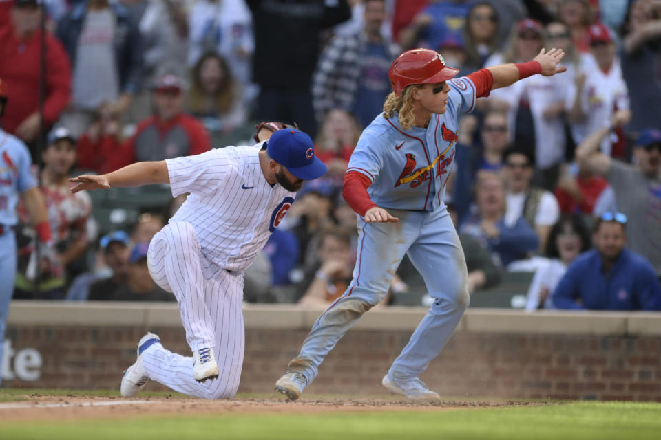 St. Louis Cardinals' Harrison Bader, right, reacts after scoring on a wild pitch while Chicago Cubs closing pitcher Tommy Nance, left, attempts to apply the tag during the ninth inning of a baseball game Saturday, Sept. 25, 2021, in Chicago. St. Louis won 8-5. (AP Photo/Paul Beaty)