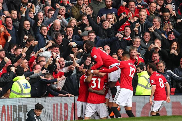 Manchester United players celebrate one of Marcus Rashford's two goals in a 2-1 victory over Liverpool. (Getty)
