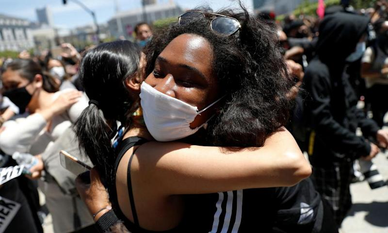 Protesters embrace during a rally in San Francisco on Monday.