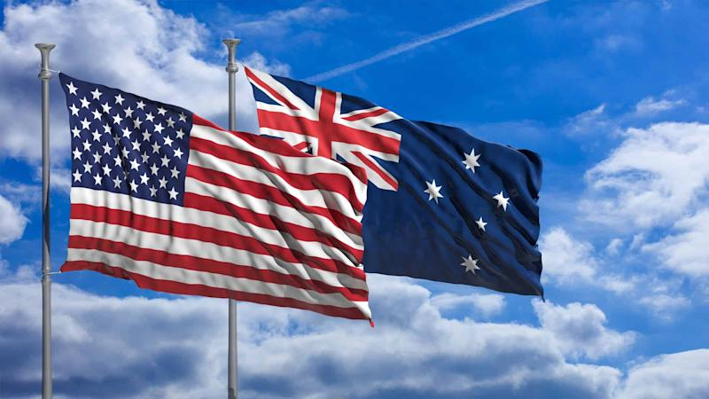 American and Australian flags flying against blue sky