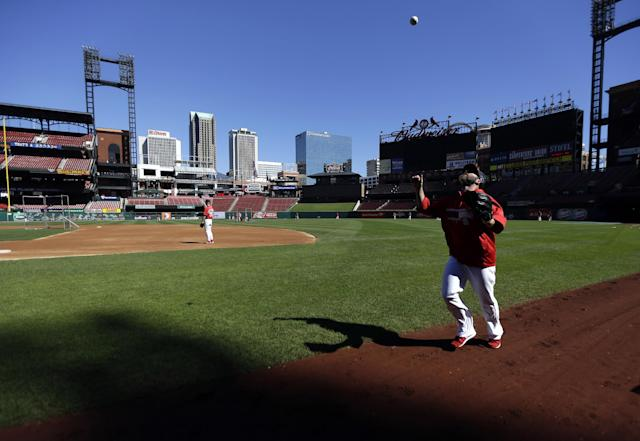 St. Louis Cardinals pitcher Jason Motte tosses a ball in the air as he runs off the field near the end of a short workout Tuesday, Oct. 8, 2013, in St. Louis. Game 5 of the National League division series baseball playoff between the Pirates and the St. Louis Cardinals is scheduled for Wednesday. (AP Photo/Jeff Roberson)