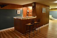 """<p>If a white space isn't your thing, you can always embrace your brown wood paneling and lean into a retro aesthetic. This blogger uses string lights, vintage prints, and a shuffleboard table to achieve a self-described """"1970s went to summer camp"""" look. </p><p><strong>See more at <a href=""""https://bridgetsbeehive.com/rumpus-room-basement-reveal/"""" rel=""""nofollow noopener"""" target=""""_blank"""" data-ylk=""""slk:Bridget's Beehive"""" class=""""link rapid-noclick-resp"""">Bridget's Beehive</a>. </strong></p><p><a class=""""link rapid-noclick-resp"""" href=""""https://go.redirectingat.com?id=74968X1596630&url=https%3A%2F%2Fwww.walmart.com%2Fip%2FHoliday-Time-Indoor-and-Outdoor-Clear-Mini-Christmas-Lights-59-300-Count-Green-Wire%2F995323450&sref=https%3A%2F%2Fwww.redbookmag.com%2Fhome%2Fg36061437%2Fbasement-ideas%2F"""" rel=""""nofollow noopener"""" target=""""_blank"""" data-ylk=""""slk:SHOP STRING LIGHTS"""">SHOP STRING LIGHTS</a></p>"""