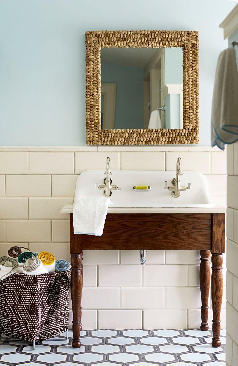 <p>Pastel blue is a no-fail choice to pair with cream and wood tones. Here, large cream tiles ground this bathroom, while soft blue patterned floor tiles add a dose of drama.</p>