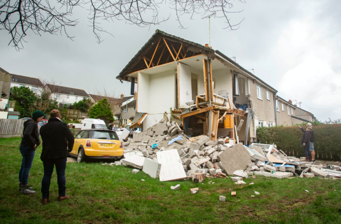 Onlookers stand outside the house following the explosion on Wednesday. (SWNS)