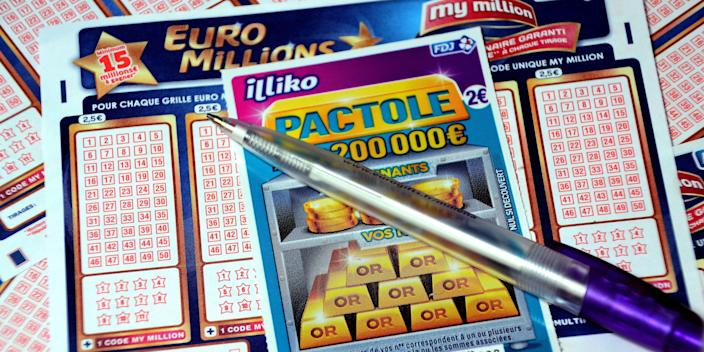 In this photo illustration is a pen and a scratch card on Euromillions tickets.