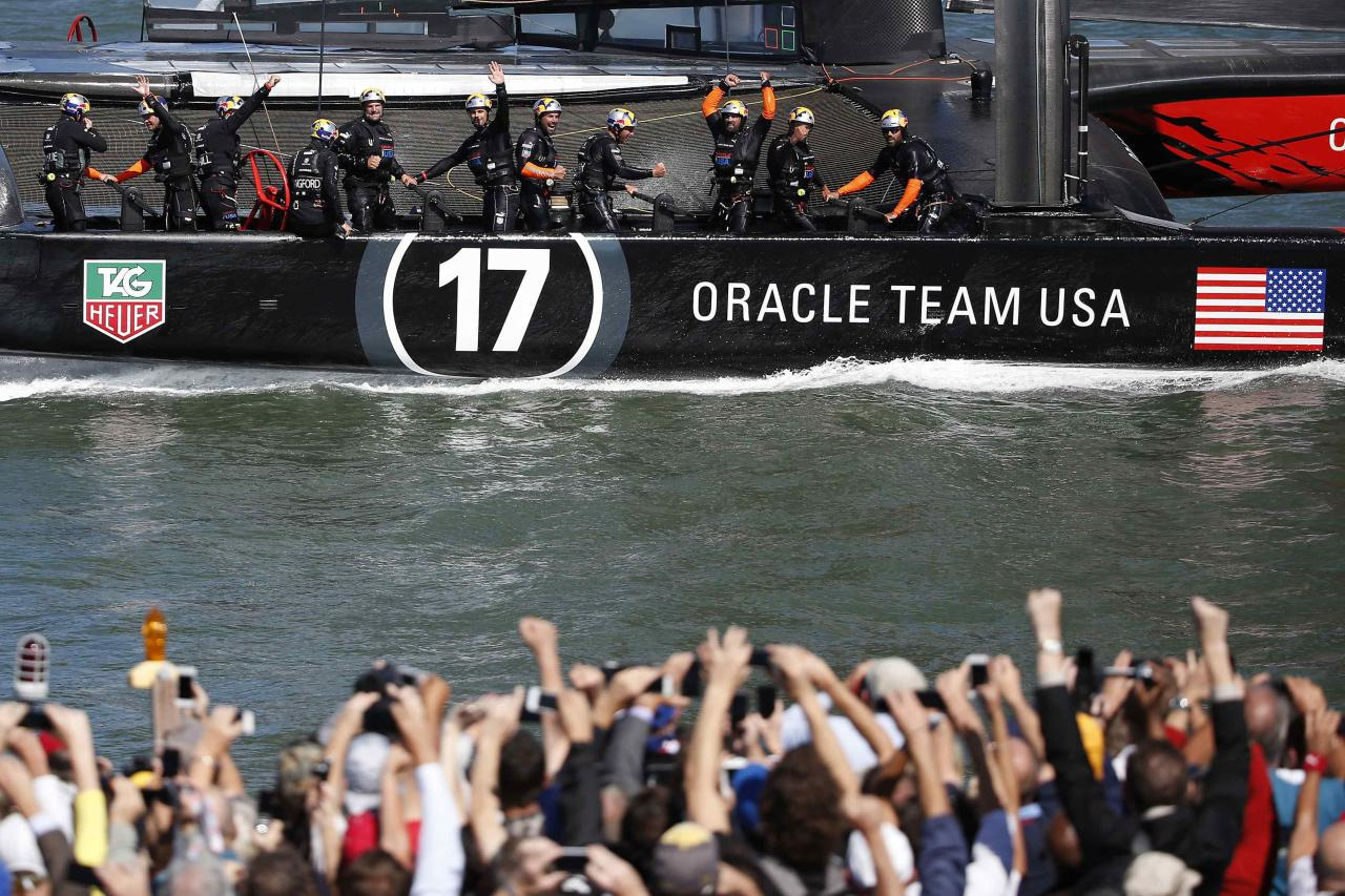 Members of Oracle Team USA wave to spectators after winning Race 18 of the 34th America's Cup yacht sailing race against Emirates Team New Zealand in San Francisco