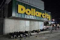 """Salvadoran migrants huddled on the sidewalk in front of a shop called """"Dollarcity"""" before a caravan departed"""