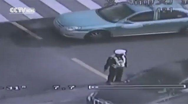 The officer stood close to the crack as he shepherded cars away. Source: CCTV