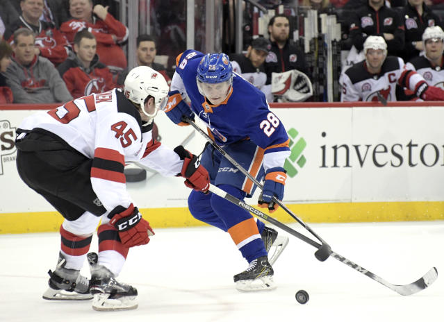 New Jersey Devils defenseman Sami Vatanen (45) stick checks New York Islanders defenseman Sebastian Aho (28) during the first period of an NHL hockey game Saturday, Feb. 24, 2018, in Newark, N.J. (AP Photo/Bill Kostroun)
