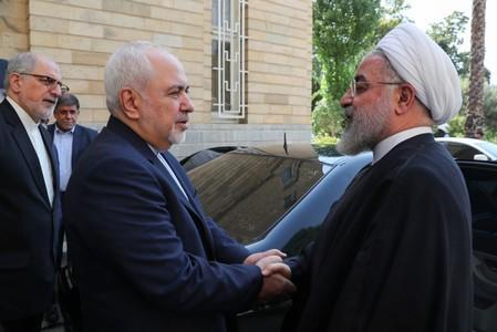 Iranian President Hassan Rouhani shakes hands with Iran's Foreign Minister Mohammad Javad Zarif in Tehran