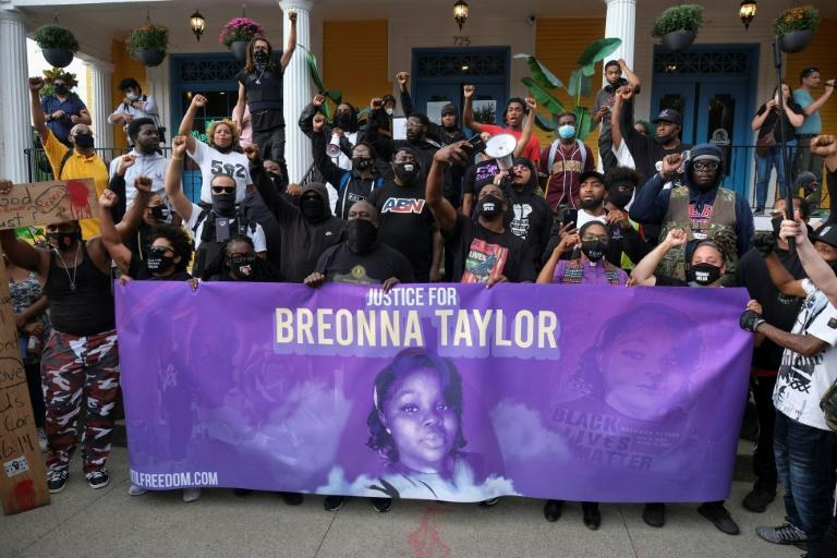 Demonstrators stand in front of a local restaurant on a third day of protests over the lack of criminal charges in the police killing of Breonna Taylor and the result of a grand jury inquiry, in Louisville, Kentucky, on September 25, 2020