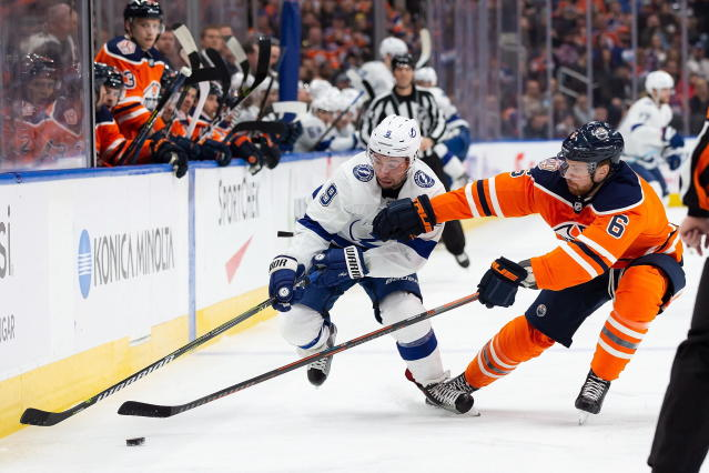 Edmonton Oilers defenseman Adam Larsson, right, competes for the puck Tampa Bay Lightning center Tyler Johnson during the first period of an NHL hockey game Saturday, Dec. 22, 2018, in Edmonton, Alberta. (Codie McLachlan/The Canadian Press via AP)