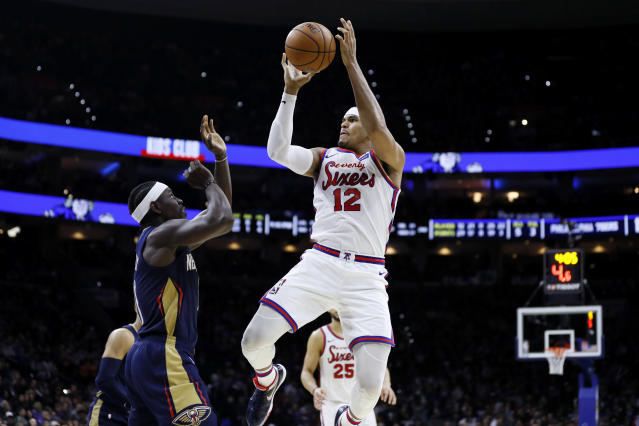 Philadelphia 76ers' Tobias Harris (12) tries to shoot past New Orleans Pelicans' Jrue Holiday during the second half of an NBA basketball game, Friday, Dec. 13, 2019, in Philadelphia. (AP Photo/Matt Slocum)