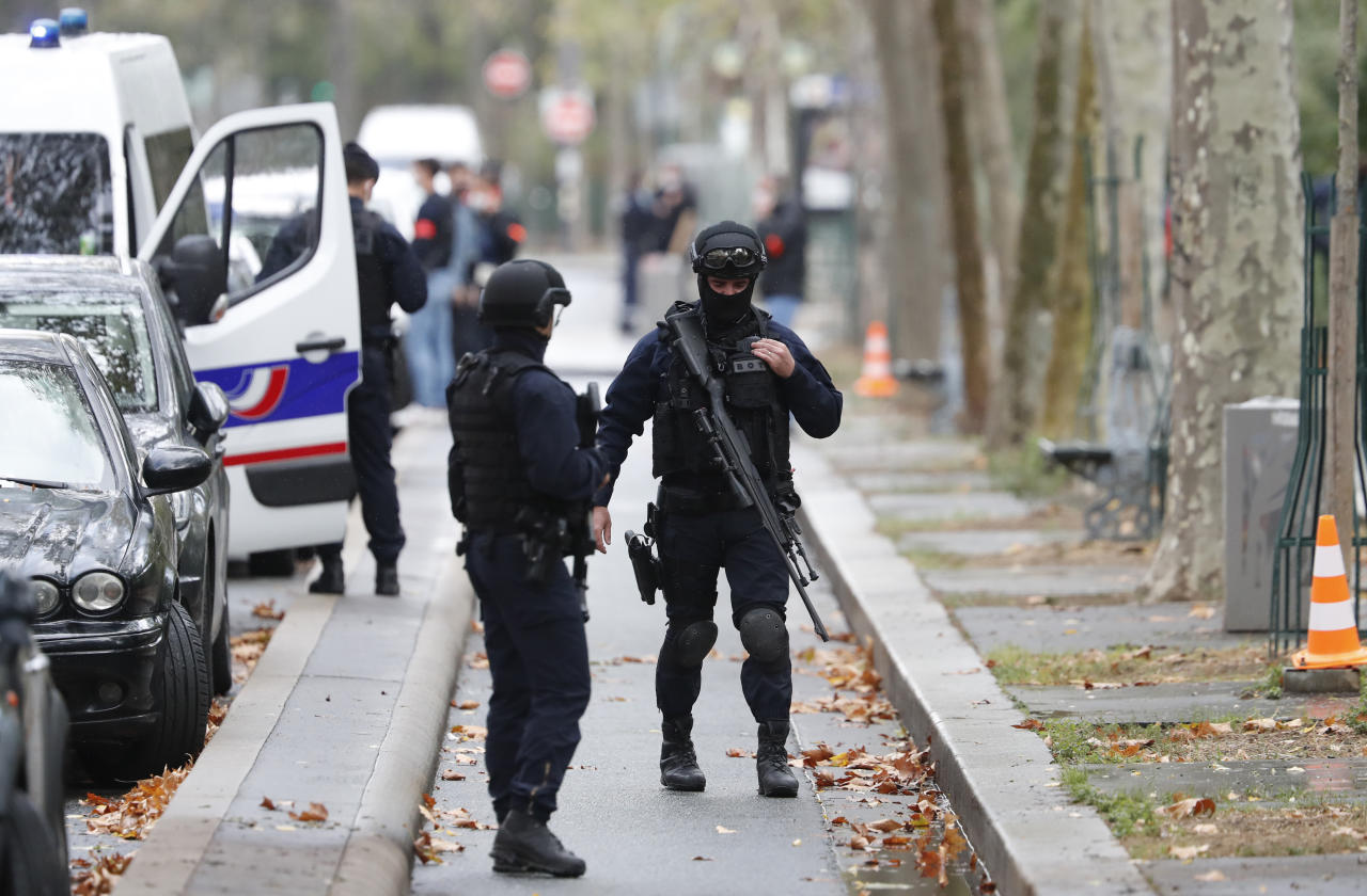 "Riot police officers arrive after four people have been wounded in a knife attack near the former offices of satirical newspaper Charlie Hebdo, Friday Sept. 25, 2020 in Paris. A police official said officers are ""actively hunting"" for the perpetrators and have cordoned off the area including the former Charlie Hebdo offices after a suspect package was noticed nearby. Islamic extremists attacked the offices in 2015, killing 12 people. (AP Photo/Thibault Camus)"