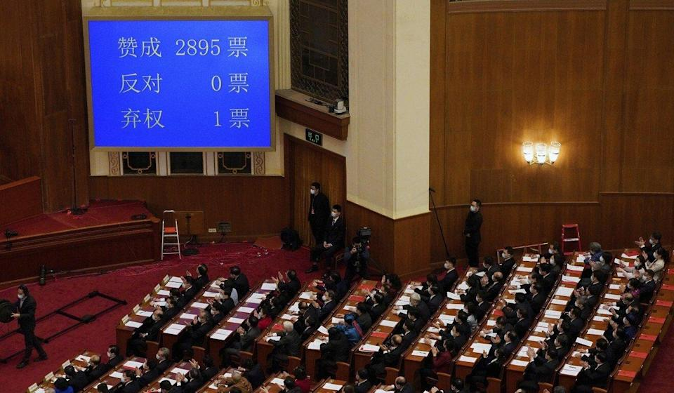 Delegates in Beijing applaud near a screen showing number of votes supporting the plan to give a pro-Beijing committee power to appoint more of Hong Kong's lawmakers. Photo: AP