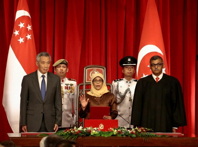 Halimah Yacob (C), a former speaker of parliament from the Malay Muslim minority, won the presidency in a walkover after authorities decided her rivals did not meet strict eligibility criteria