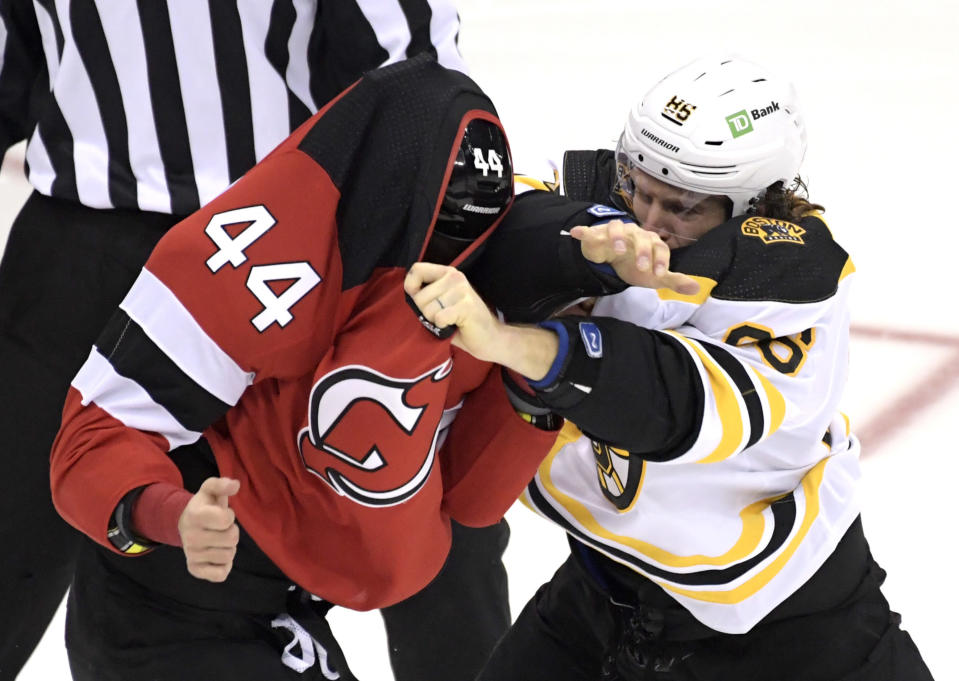 Boston Bruins defenseman Kevan Miller, right, fights with New Jersey Devils left wing Miles Wood (44) during the first period of an NHL hockey game Saturday, Jan. 16, 2021, in Newark, N.J. (AP Photo/Bill Kostroun)
