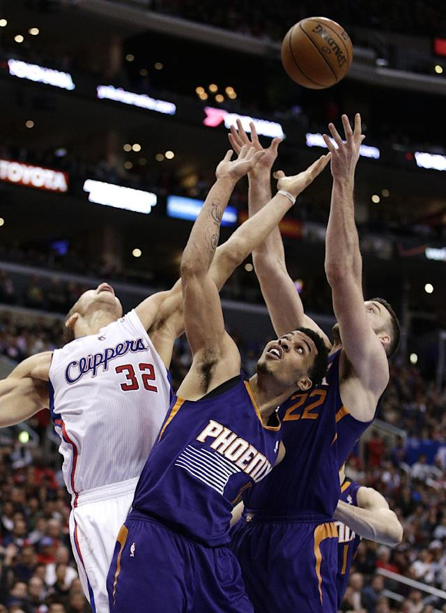 Los Angeles Clippers' Blake Griffin, left, fights for a rebound with Phoenix Suns' Gerald Green, center, and Miles Plumlee during the first half of an NBA basketball game on Monday, Dec. 30, 2013, in Los Angeles. (AP Photo/Jae C. Hong)