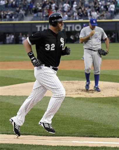 Chicago White Sox's Adam Dunn, left, heads for home after hitting a home run off Kansas City Royals starting pitcher Felipe Paulino, right, during the first inning of a baseball game, Friday, May 11, 2012, in Chicago. (AP Photo/Charles Rex Arbogast)