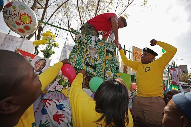 PRETORIA, SOUTH AFRICA - JUNE 27: Members of the ANC Youth League hang a banner outside the Mediclinic Heart Hospital where former President Nelson Mandela is being treated for a recurring lung infection June 27, 2013 in Pretoria, South Africa. Family members and President Jacob Zuma have visited Mandela during his 20th day in the hospital. (Photo by Chip Somodevilla/Getty Images)