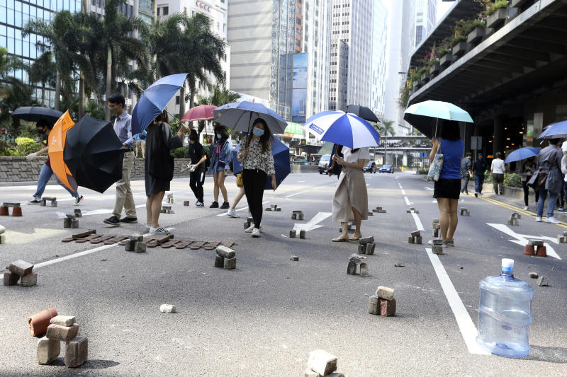 Demonstrators walk past bricks piled as traffic barricades on a road during a protest in the financial district in Hong Kong, Friday, Nov. 15, 2019. Protesters who have barricaded themselves in a Hong Kong university partially cleared a road they were blocking and demanded that the government commit to holding local elections on Nov. 24. (AP Photo/Achmad Ibrahim)