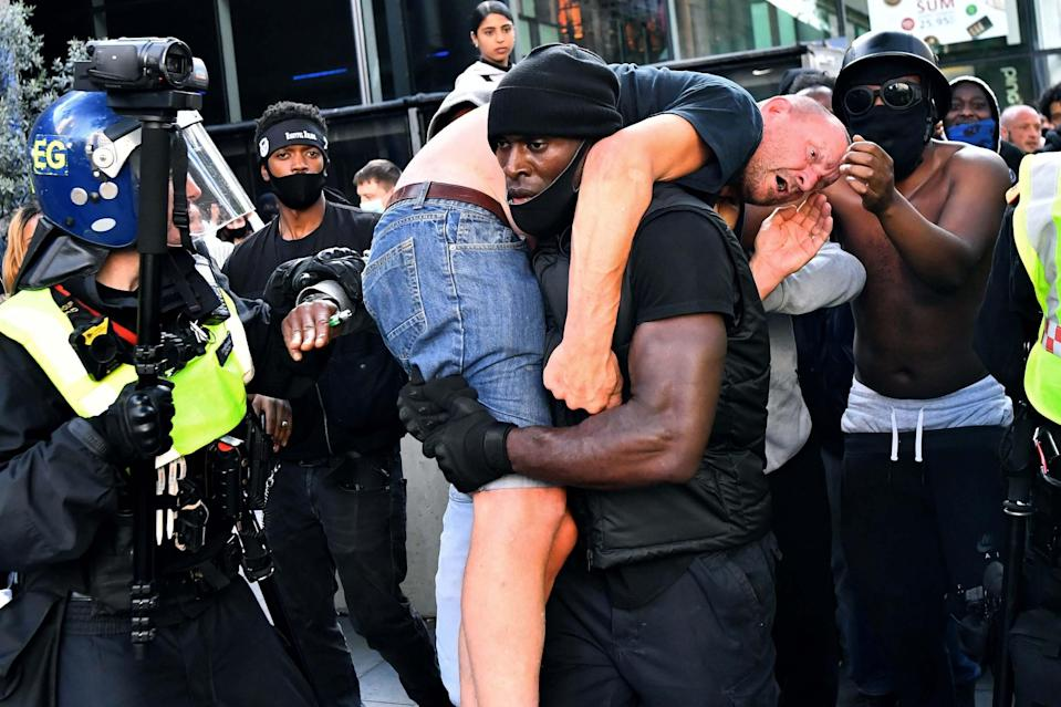 The image of father-of-two Mr Hutchinson rescuing Bryn Male during race violence in June as shared widely around the world (REUTERS)