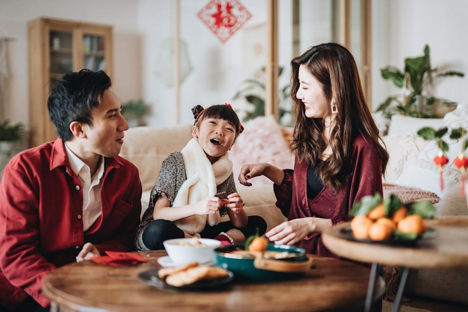 Lovely daughter chatting joyfully with father and mother and enjoying family bonding time while celebrating Chinese New Year at home