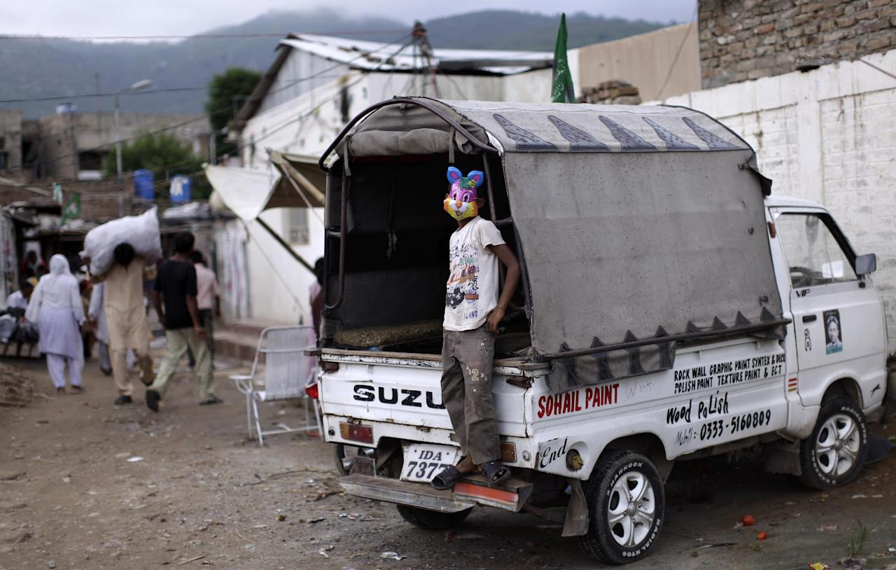 A Pakistani Christian youth wearing a mask, stands in a vehicle in a Christian neighborhood in Islamabad, Pakistan, Monday, Aug. 20, 2012. Pakistani authorities arrested a Christian girl and are investigating whether she violated the country's strict blasphemy laws after furious neighbors surrounded her house and demanded police take action, a police officer said Monday. The arrest of the girl and outrage among the local community demonstrates the deep emotion that suspected blasphemy cases can evoke in this conservative Muslim country, where rising extremism often means religious minorities live in fear of persecution.(AP Photo/Muhammed Muheisen)